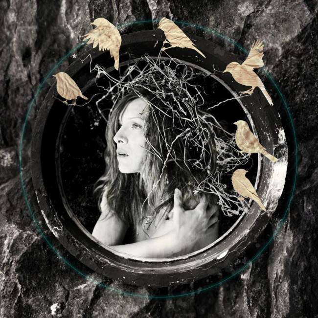 Eine Frau mit Gestrüpp auf dem Kopf schaut durch ein Steinfenster, um ihren Kopf haben sich sechs Papiervögel versammelt.