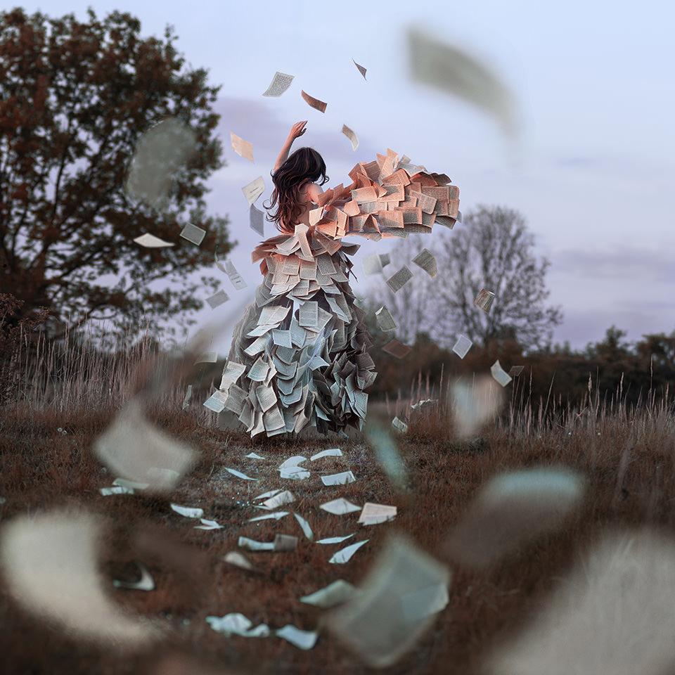 Eine Frau in einem Kleid aus Buchseiten rennt weg. Die Buchseiten fliegen um sie herum.
