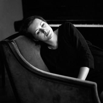 Ein Mensch auf einem Sessel und im Hintergrund ein Klavier.