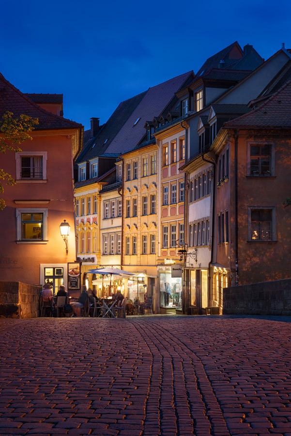 Mit Kopfsteinen gepflasterter Weg führt durch eine Gasse mit historischen Häusern