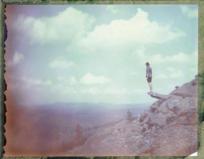 Ein Mann steht auf einem Felsvorsprung und schaut in die Weite.