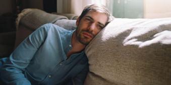 Ein Mann liegt weinen auf einem Sofa