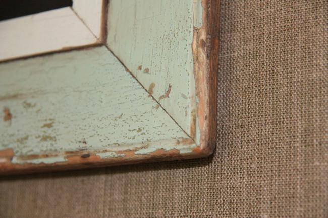 Blick auf die Ecke eines alten mintgrünen Bilderrahmens.