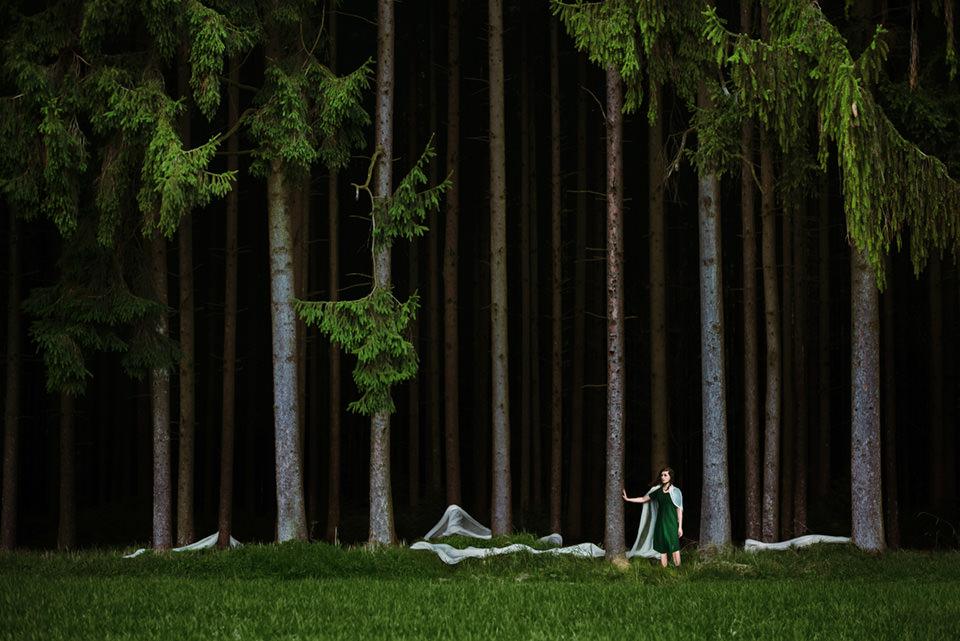Eine Frau steht am Waldrand. Ihr langer Umhang liegt über dem Waldboden zwischen den Bäumen.