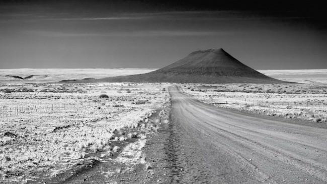 Straße durch eine karge Steppe, die auf einen Berg zuführt.