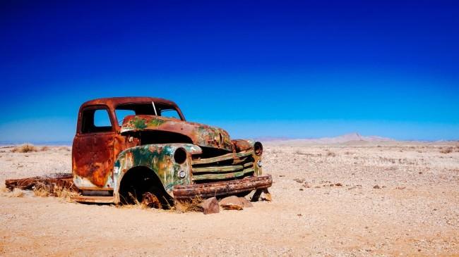 Verrostetes Auto in der Wüste vor blauem Himmel.
