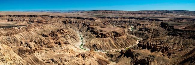 Canyonlandschaft vor blauem Himmel.