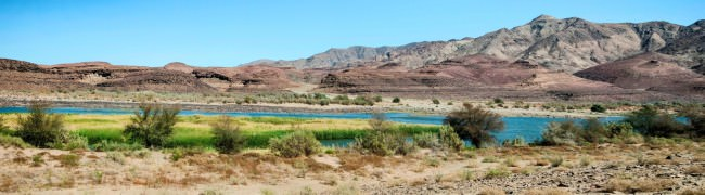 Panorama eines Flusses mit grüner Umgebung in sonst trockener Steppe.
