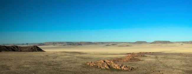 Wüstenlandschaft mit einzelnen Plateaus vor blauem Himmel.