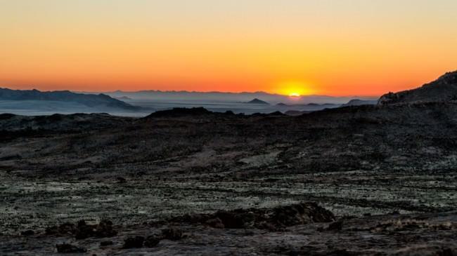 Sonnenaufgang über einer hügeligen Landschaft.