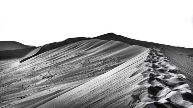 Dünenlandschaft mit Fußspuren im Vordergrund.