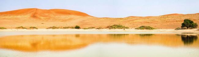 Blick üder die Oberfläche eines Sees vor oranger Dünenlandschaft.