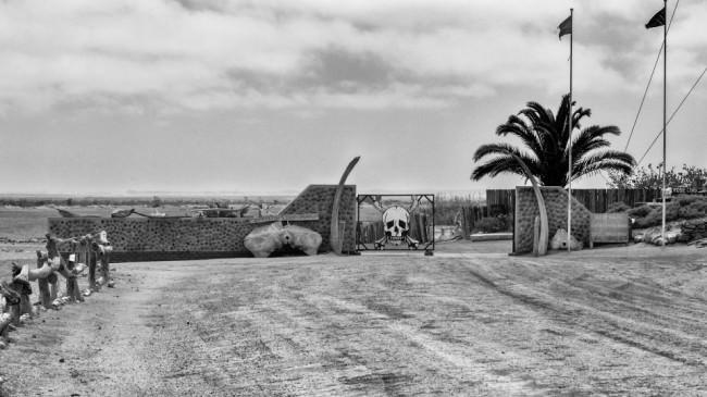 Einfahrt zu einem Hof in der Wüste, am Tor das große Bild eines Totenschädels.