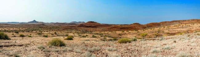 Steppenlandschaft, im Hintergrund mit Hügeln und Gebirge.