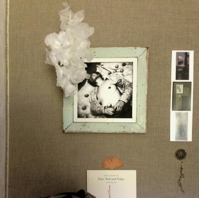Ein Bild hängt in einem Bilderrahmen an der Wand. Daneben sind noch andere Bilder zu sehen.