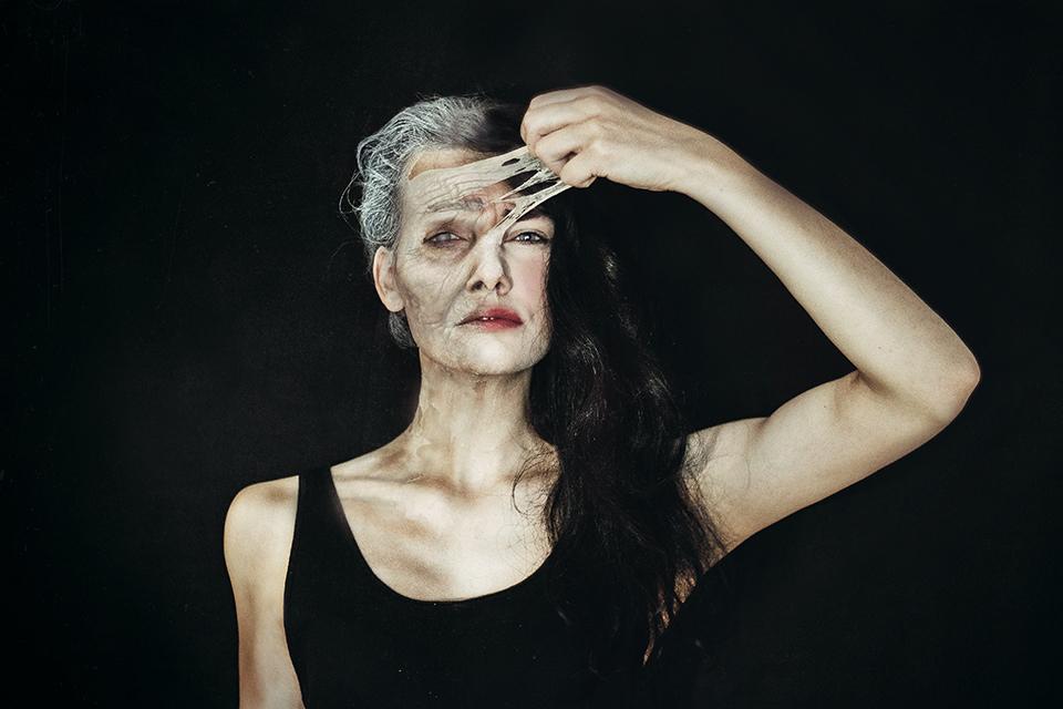 Eine Frau ist halb alt und halb jung und zieht mit einer Hand die alte Haut von ihrem Gesicht ab.