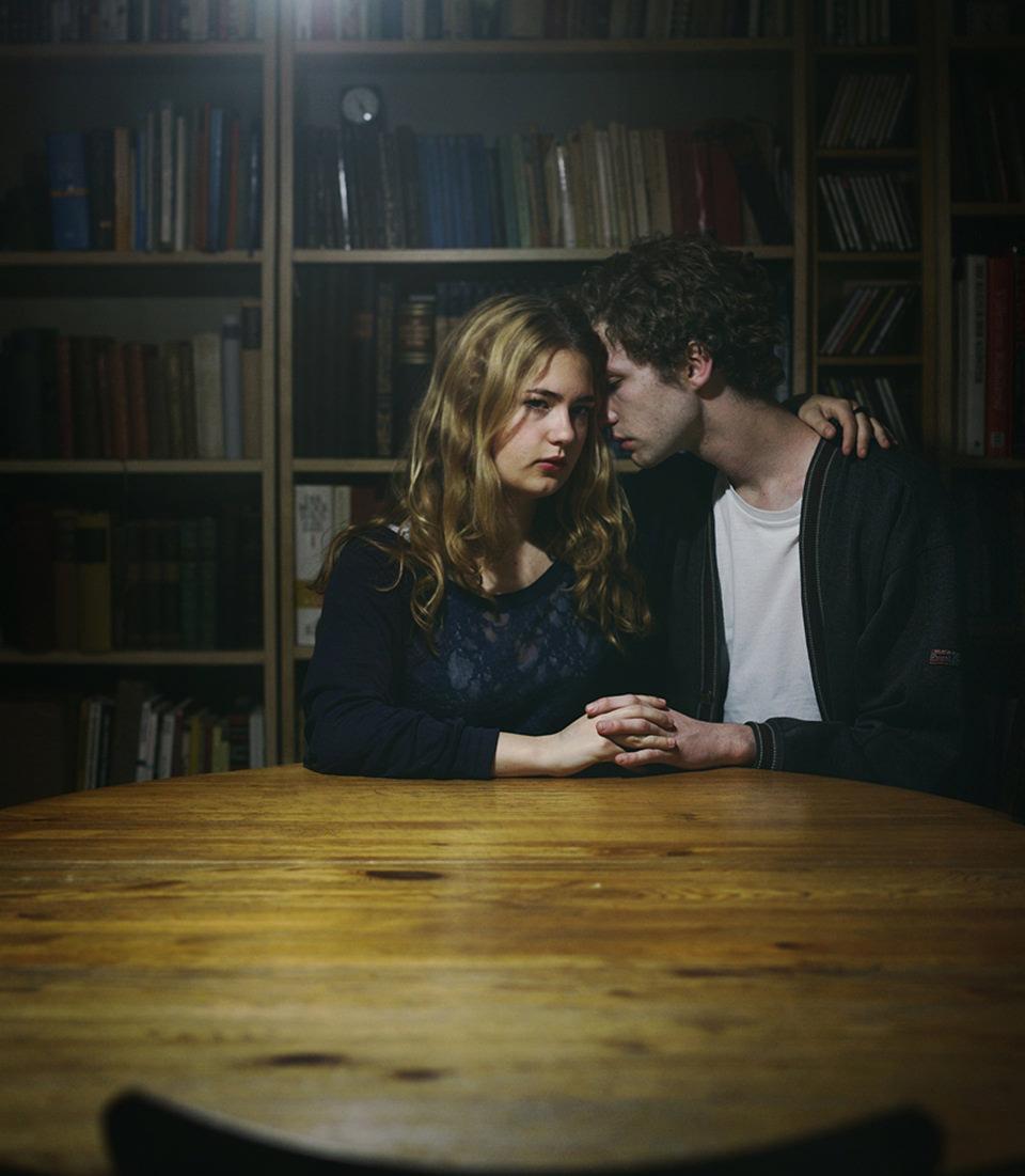 Ein Mann und eine Frau sitzen am Tisch und halten sich an den Händen.