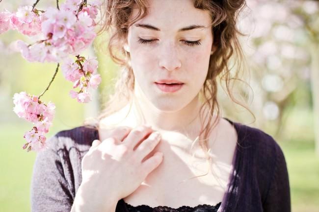 Eine Frau steht unter Kirschblüten mit geschlossenen Augen.