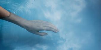 Eine Hand greift ins Wasser, indem sich die Wolken spiegeln.