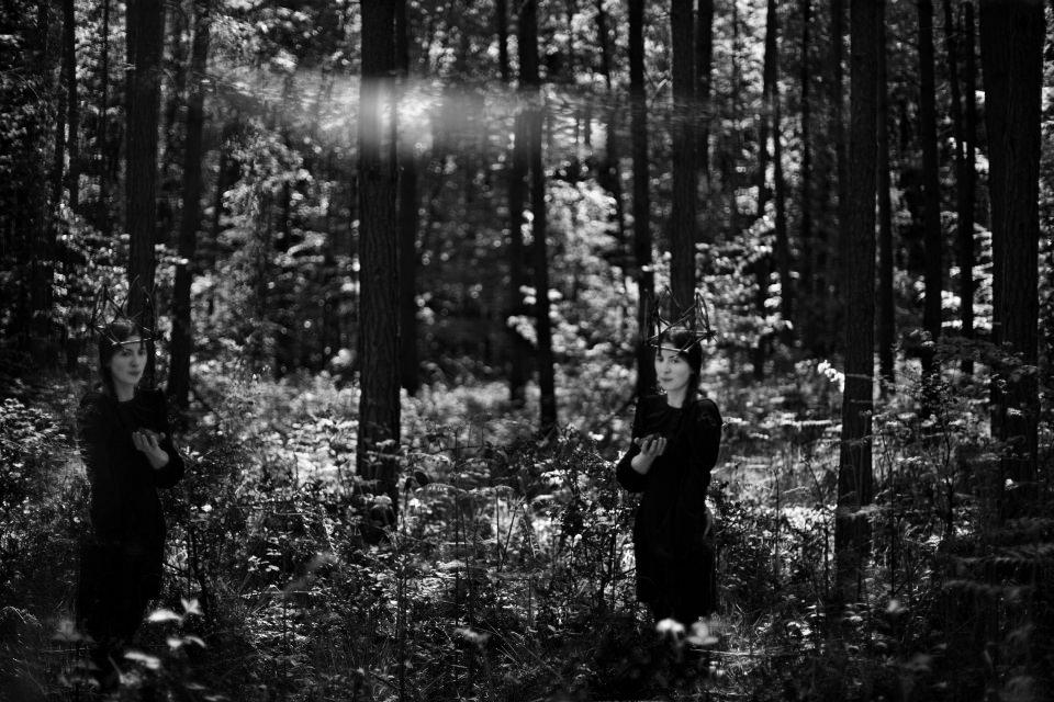Ein Mädchen mit Holzkrone steht im Wald.
