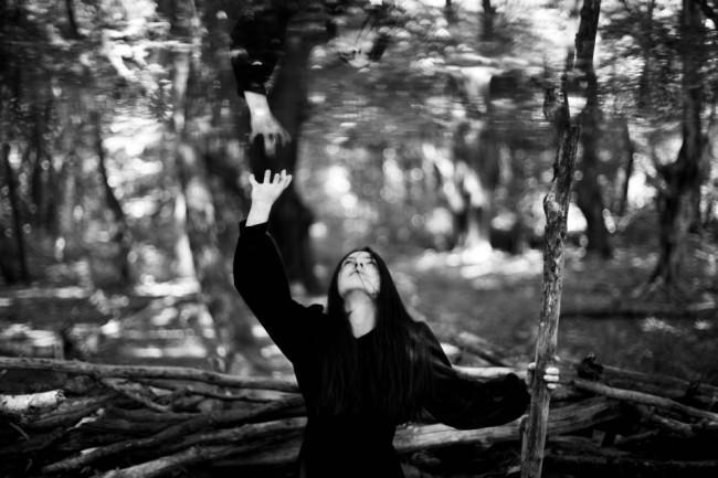 Ein Mädchen hält mit einer Hand einen Stab und greift mit der anderen zu ihrem eigenen Spiegelbild über sich.