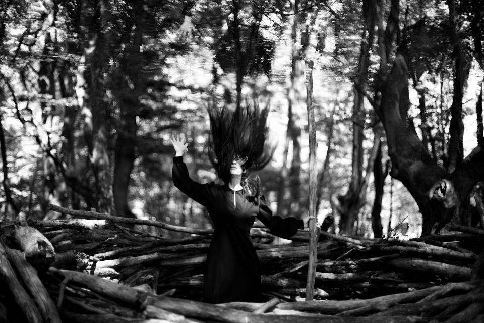 Ein Mädchen hält mit einer Hand einen Stab und greift mit der anderen zu ihrem eigenen Spiegelbild über sich, ihre Haare fliegen.