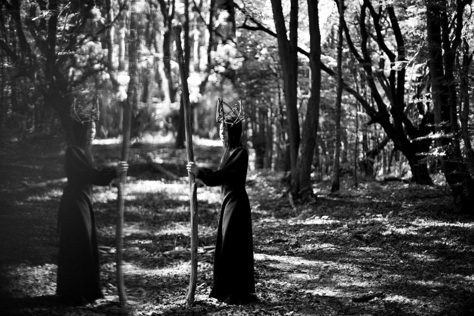 Ein Mädchen in langem schwarzen Kleid steht mit einem Stab und einer Holzkrone im Wald.