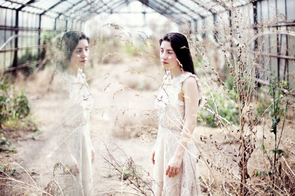 Ein Mädchen in einem weißen Kleid steht in einem leeren Gewächshaus.