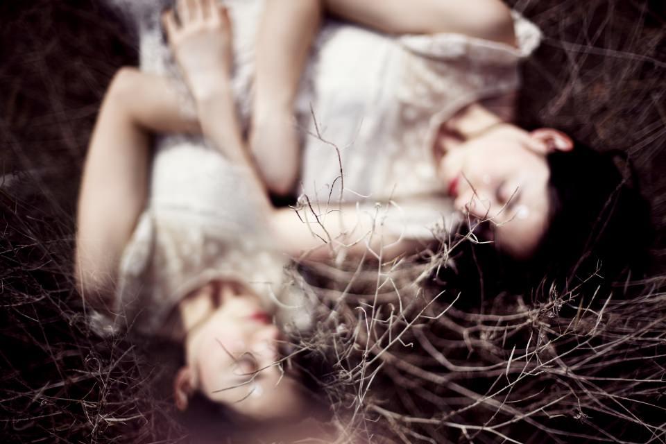 Ein Mädchen in weißem Kleid liegt im Gras.