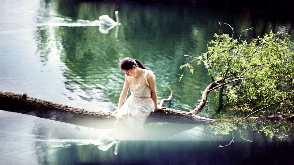 Ein Mädchen in weißem Kleid sitzt auf einem Baumstamm, der ins Wasser ragt.