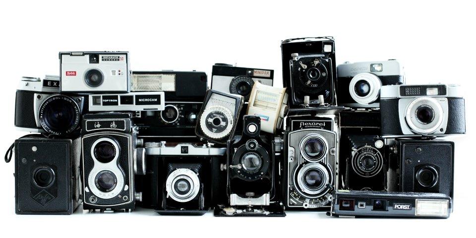 Viele alte Fotoapparate, aufgereiht und aufgetürmt.