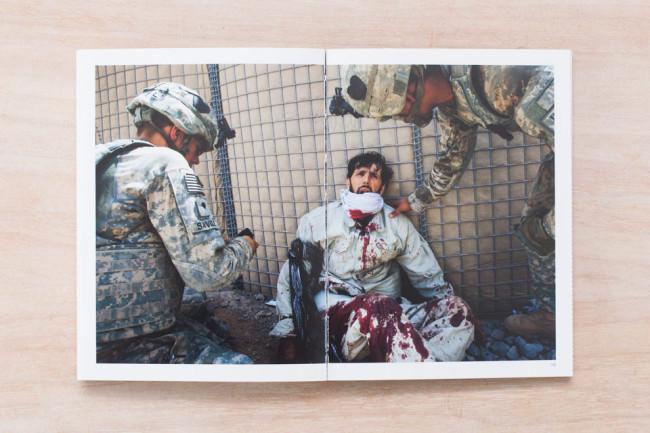 Ein verletzter Soldat wird von zwei anderen Soldaten begutachtet.
