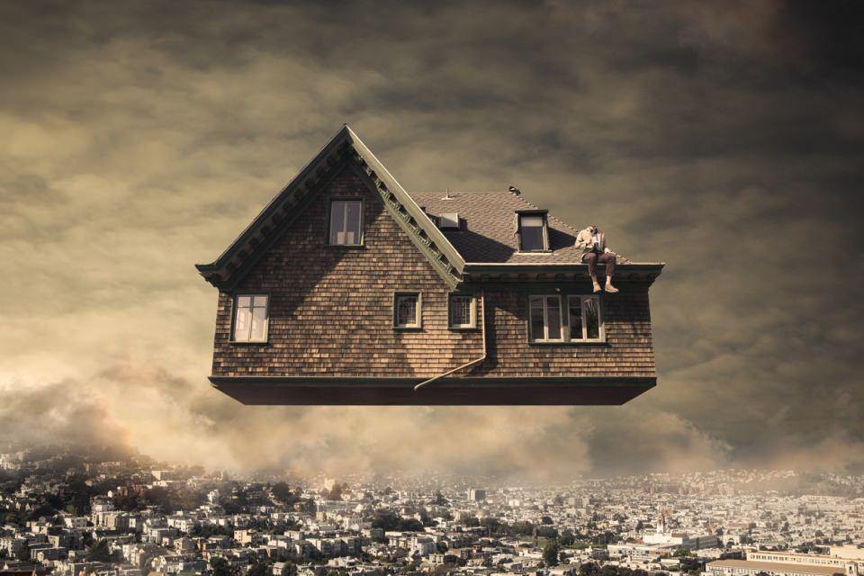 Ein kopfloser Mann sitzt auf dem Dach eines Hauses, das über einer Stadt schwebt.