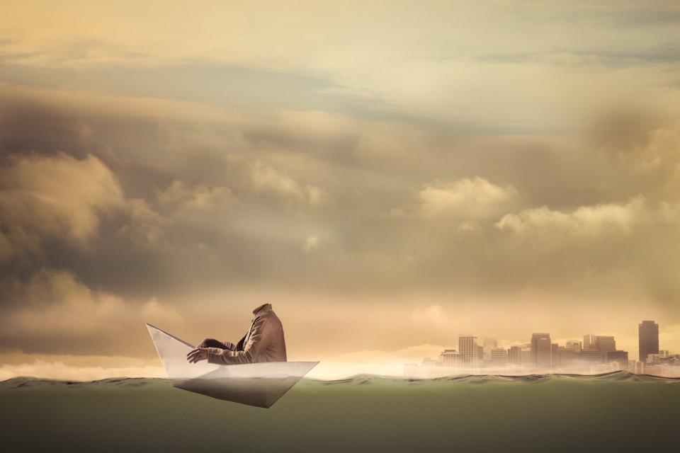 Ein kopfloser Mann sitzt in einem Papierboot, das auf dem Wasser schwimmt.