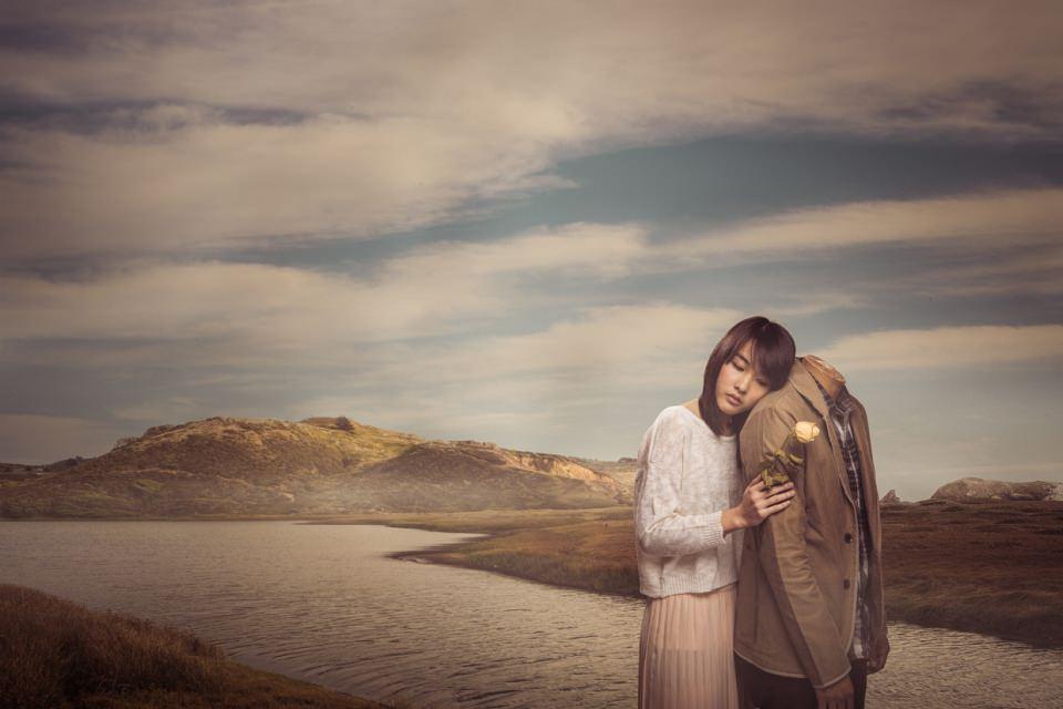 Ein Mädchen mit einer Rose in der Hand schmiegt sich an einen kopflosen Mann, sie stehen am Ufer eines Flusses.