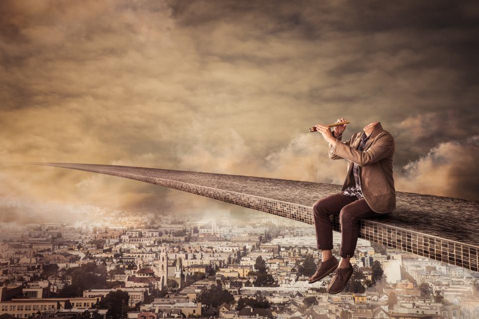 Ein kopfloser Mann sitzt auf einem über einer Stadt schwebenden Weg und schaut durch ein Fernrohr.