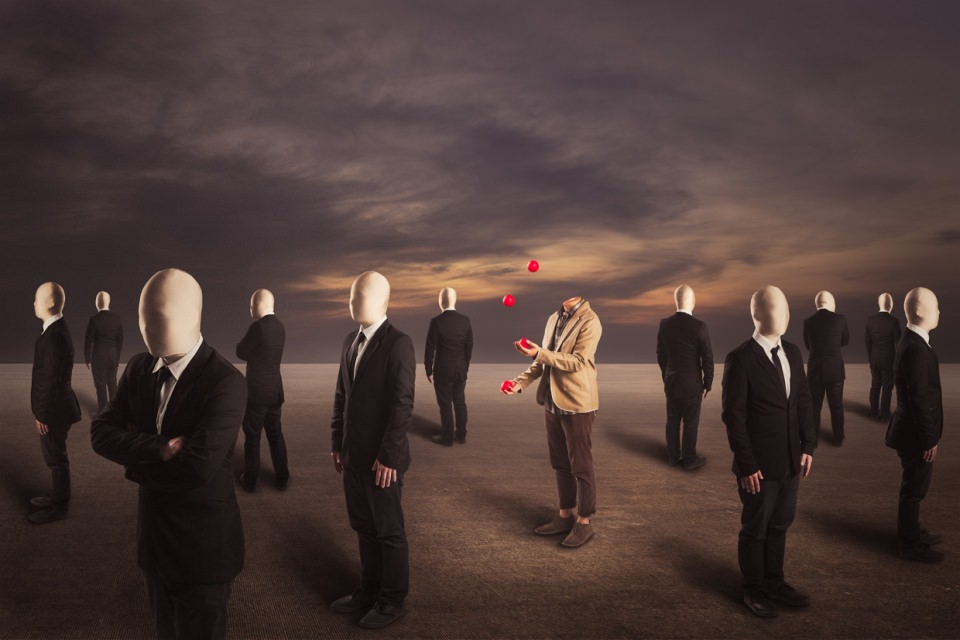Ein kopfloser Mann jongliert mit roten Bällen, um ihn herum stehen gesichtslose Männer in Anzügen.
