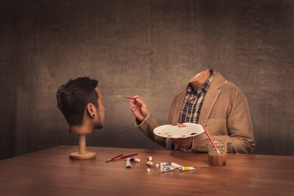 Ein kopfloser Mann sitzt an einem Tisch und malt mit Pinsel und Farbe an einem Kopf, der vor ihm steht.