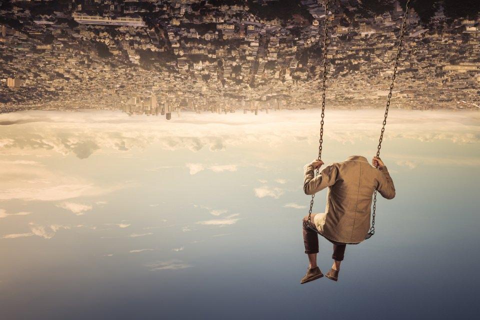 Ein kopfloser Mann sitzt auf einer Schaukel, die an einer Stadt über ihm hängt, unter ihm der Himmel.
