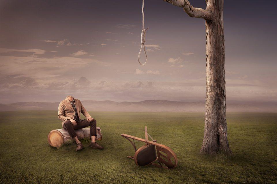 Ein kopfloser Mann sitzt vor einem Baum, an dem ein Strick hängt, darunter ein umgekippter Stuhl.