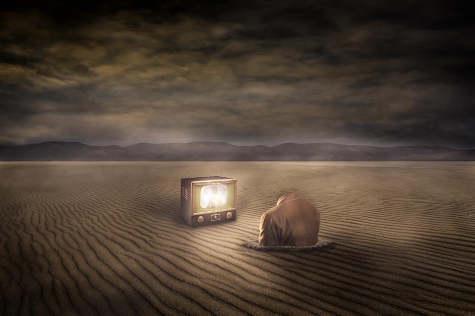 Ein kopfloser Mann steckt bis zur Brust in Wüstensand und schaut auf einen vor ihm stehenden Fernsehbildschirm.