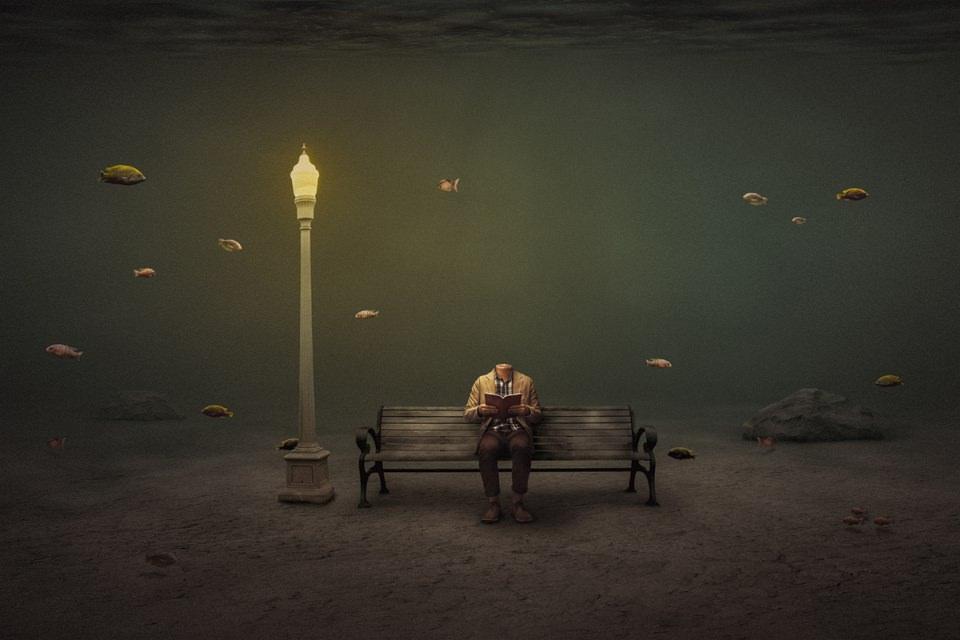 Ein kopfloser Mann liest im Licht einer Straßenlaterne auf einer Bank ein Buch, um ihn schwimmen Fische.