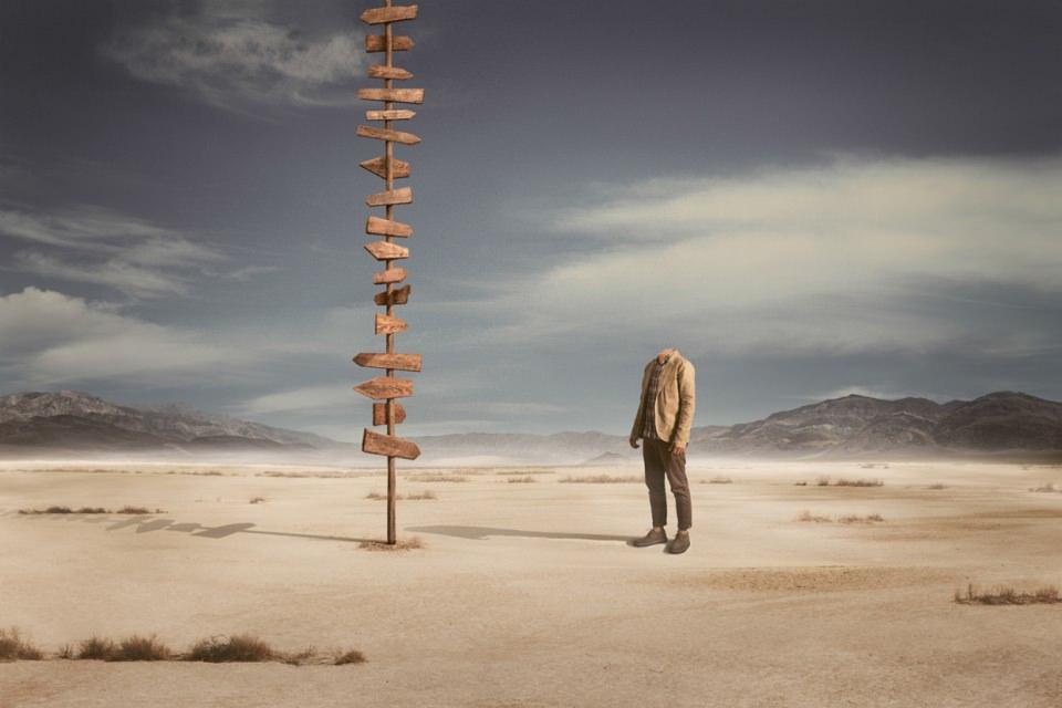 Ein kopfloser Mann steht in einer Wüste vor einem Pfahl, an dem sehr viele leere Wegweiser angebracht sind.