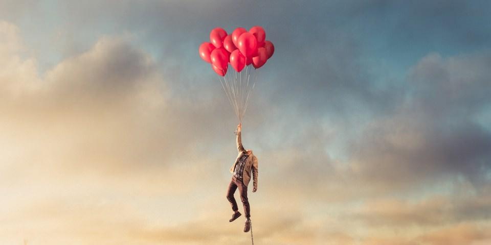 Ein kopfloser Mann schwebt an einem Strauß roter Luftballons über einer Stadt, an seinem Fuß führt eine Metallkette nach unten.