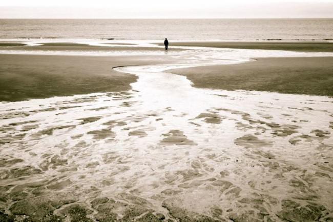 Eine Person am Meer steht klein am Horizon zentriert im Bild.