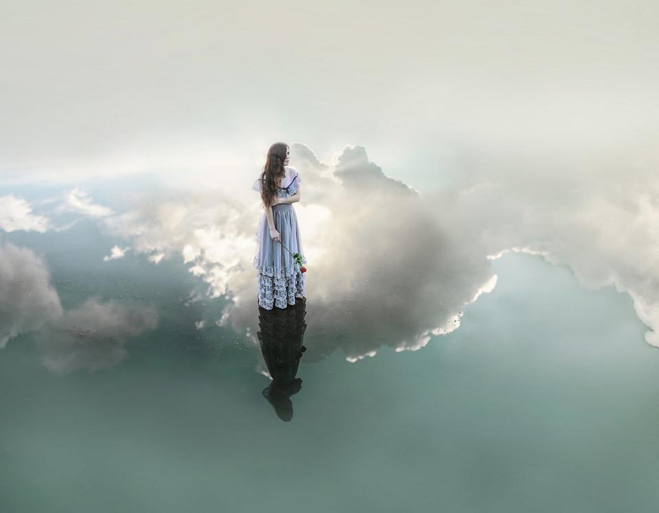Eine Frau steht in einem See aus Wolken.