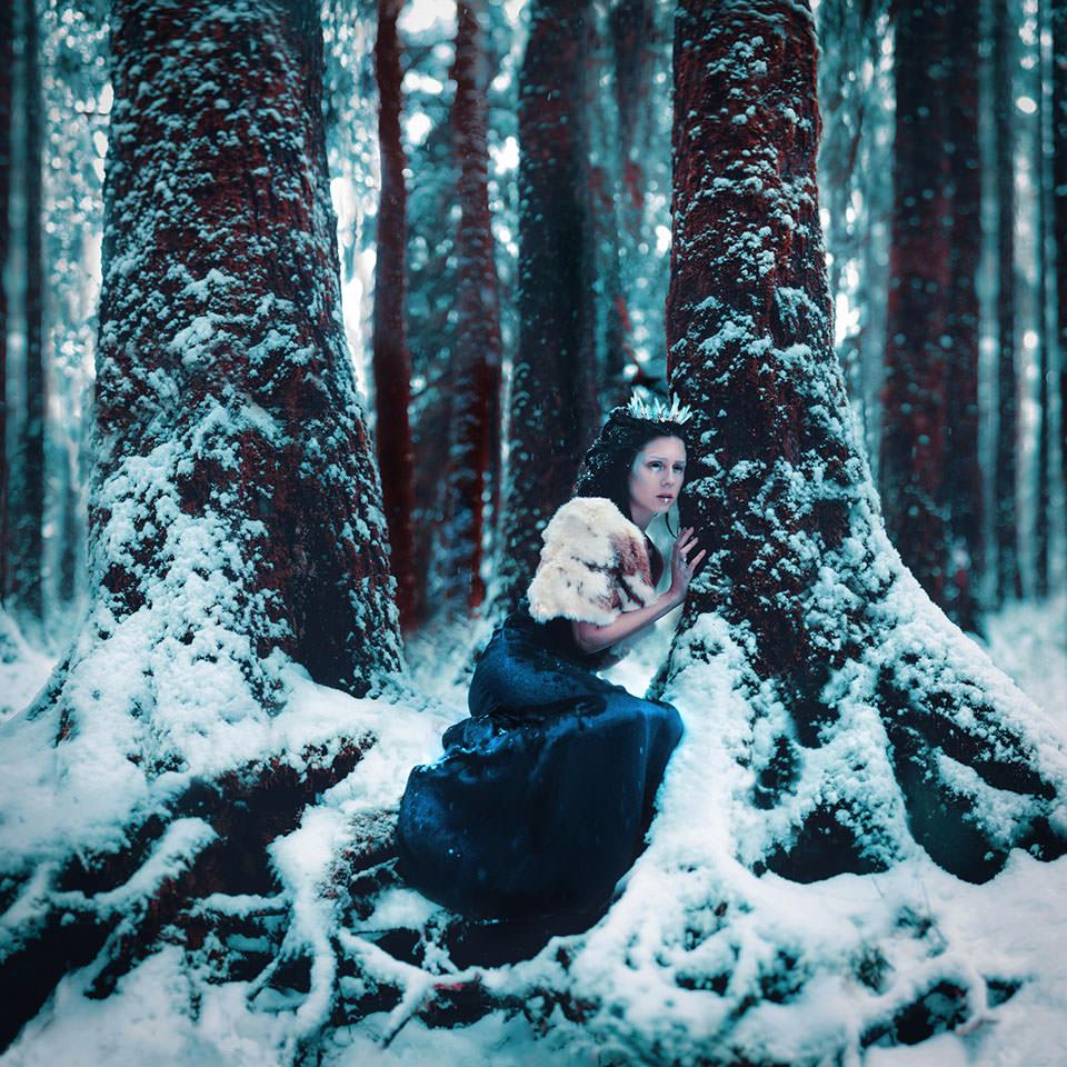 Eine Frau mit Eiskrone in einem schneebedeckten Wald zwischen zwei Bäumen.