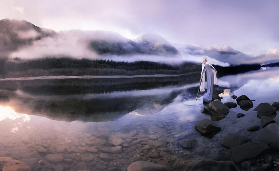 Eine Frau steht am Rand eines Sees und trägt einen langen Mantel.