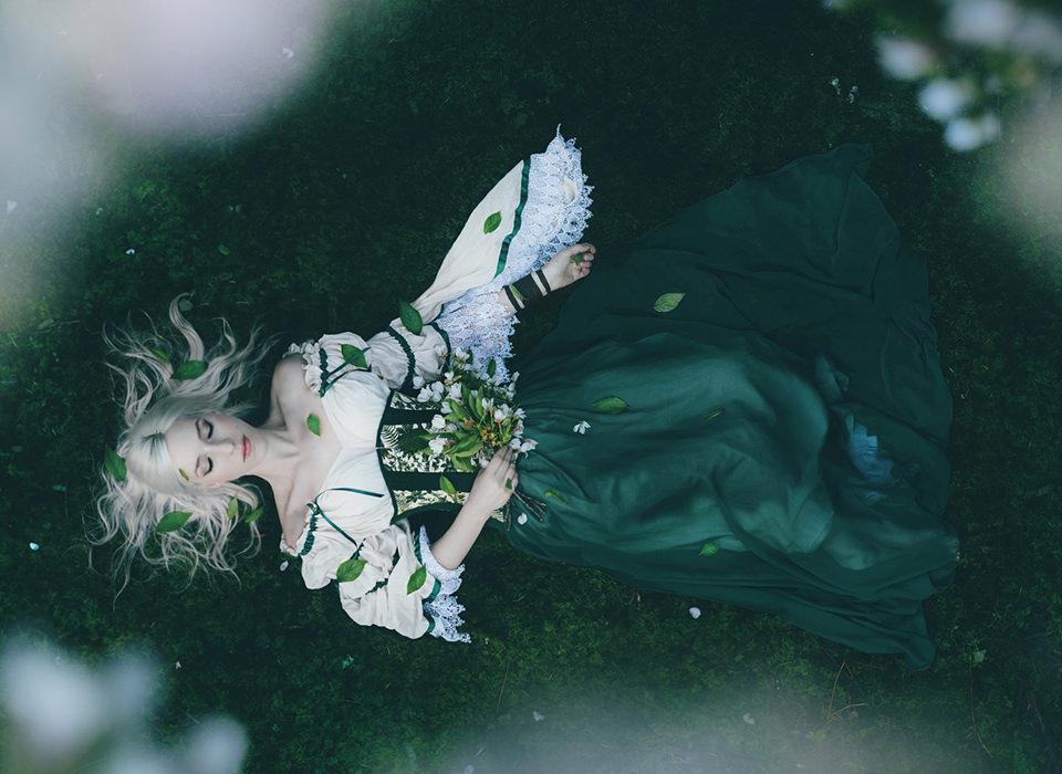 Eine Frau liegt im Gras und hält einen Blumenstrauß.