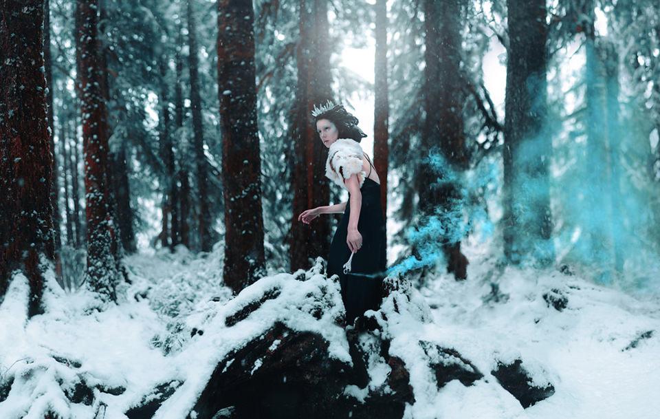 Eine Frau mit Eiskrone in einem schneebedeckten Wald.